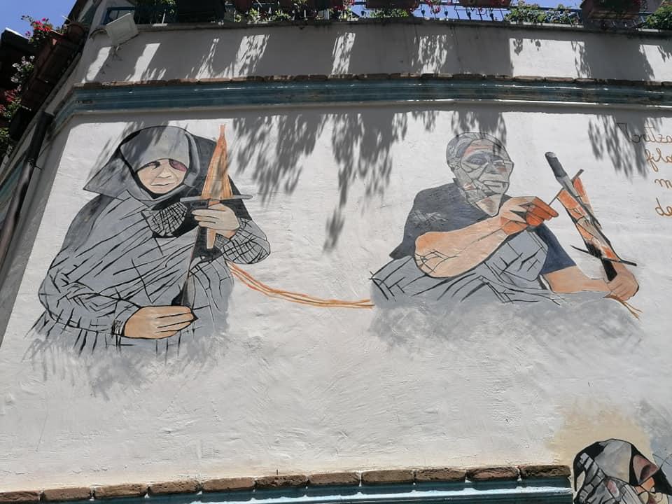 Escursione a Orgosolo: murale raffigura due anziane mentre tessono la seta